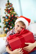 Portrait of cheerful boy with big red giftbox looking at camera on christmas eve Stock Photos