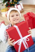 Portrait of cheerful boy in santa cap holding big red giftbox and looking at cam Stock Photos