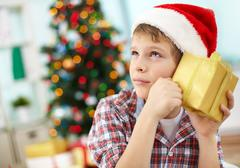 Stock Photo of portrait of pensive boy holding giftbox and guessing what is inside on christmas