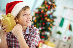 Stock Photo of portrait of smiling boy holding giftbox and guessing what is inside on christmas