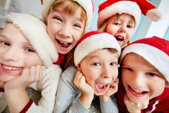 group of excited kids in santa caps looking at camera - stock photo