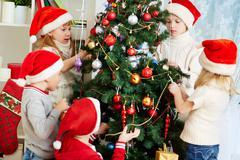 group of adorable kids in santa caps decorating xmas tree - stock photo