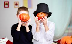 photo of twin eerie boys holding halloween pumpkins in front of their faces - stock photo