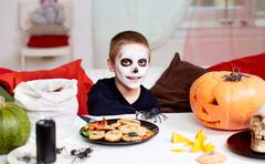 photo of eerie boy at halloween table - stock photo