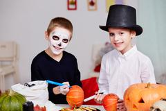 photo of two eerie boys drawing on pumpkins at halloween table - stock photo
