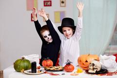 photo of twin eerie boys raising arms in joy at halloween table - stock photo