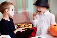 photo of two eerie boys eating cookies on halloween day - stock photo