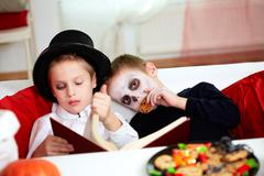 photo of two eerie boys reading and eating cookies on halloween day - stock photo