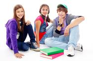 Three teenagers in casual clothes sitting in isolation Stock Photos