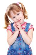 image of a sweet girl in a denim jumpsuit looking at camera - stock photo