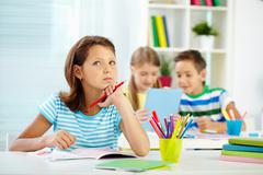 Portrait of lovely girl concentrating on drawing at workplace with schoolmates o Stock Photos