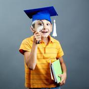 muotokuva utelias poika valmistumisen hattu silmäilyn suurennuslasilla - stock photo