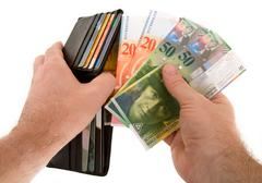 Paying cash with swiss francs currency Stock Photos