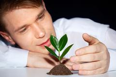 caring young man protecting green sprout from adverse conditions - stock photo