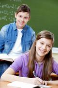 Portrait of smart girl at workplace with her classmate on background Stock Photos