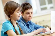 Portrait of teenage girl typing with her classmate at background Stock Photos