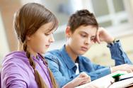Portrait of teenage girl reading book with her classmate at background Stock Photos