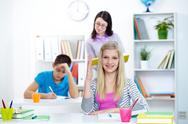 Portrait of clever teenage blonde raising arm at lesson in working environment Stock Photos