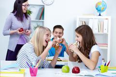 Hungry girls eating sandwiches during break in college Stock Photos
