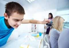 Evil lad holding black spider and going to frighten his classmates at lesson Stock Photos