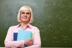 Portrait of mature teacher with copybooks looking at camera with blackboard on b Stock Photos