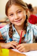 Portrait of lovely girl drawing in copybook and looking at camera Stock Photos