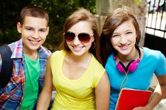 close-up portrait of three school friends smiling at camera - stock photo