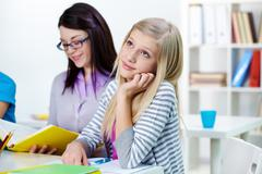 portrait of pensive teenage blonde listening to the teacher reading book at less - stock photo