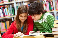 Friends spending time together studying at library Stock Photos