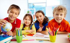 Stock Photo of group of diligent schoolchildren looking at camera in school