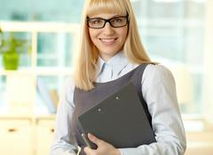 smiling woman dressed formally looking at cam with a smile and holding a clipboa - stock photo