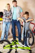 Portrait of cute boy pumping bicycle wheel with his parents on background Stock Photos