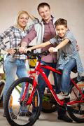 Portrait of happy family with bicycle looking at camera Stock Photos