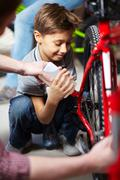 portrait of cute boy lubricating bicycle chain in garage - stock photo