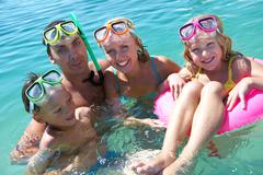 portrait of cheerful family in aqualungs looking at camera with smiles - stock photo