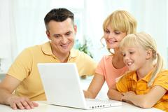 family of three using laptop together - stock photo