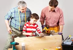 little boy trying his best in a woodshop being looked after by his dad and grand - stock photo