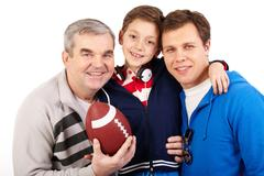 Portrait of three male family members of different age with a soccer ball Stock Photos