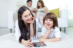 Siblings looking at camera with their parents sitting on sofa at background Stock Photos