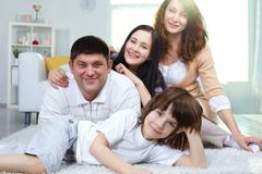 Family of four looking at camera while spending time together at home Stock Photos