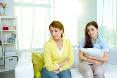 Photo of offended woman sitting on sofa with her teenage daughter being sorry fo Stock Photos