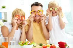 Iloinen perhe leikkii vihanneksia keittiö, terveellistä ruokaa Kuvituskuvat