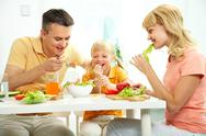 Stock Photo of family of three together at table eating fresh salad