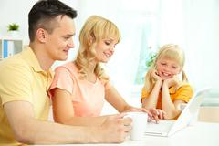 Cheerful family of three using laptop and smiling Stock Photos
