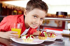 Close-up of a smiling boy with pastry and a glass of orange juice Stock Photos