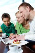 family of three spending time at a cafe surfing internet - stock photo