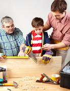 A grandfather and a father teaching a boy to work with diy Stock Photos