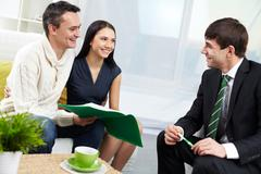 portrait of modern couple and real estate manager discussing mortgage conditions - stock photo