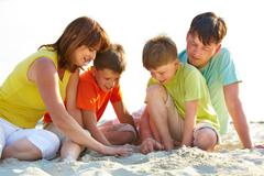 Photo of happy family sitting on sand during summer rest Stock Photos