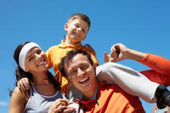 laughing family of three having fun together on a sunny summer day - stock photo
